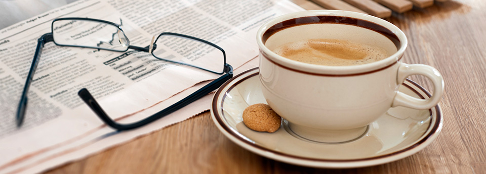 Newspaper with glasses and a cup of brewed coffee